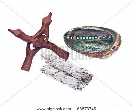 Sage smudge stick and bright polished rainbow abalone shell with wooden cobra stand isolated on white background
