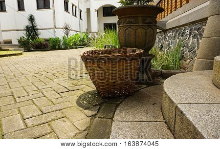 a mossy clay pot and bamboo basket abandoned at garden photo taken in Lawang Sewu Semarang Indonesia java