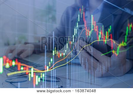 graph chart of stock market. background Business woman hand holding smartphone and using laptop computer for work in office.