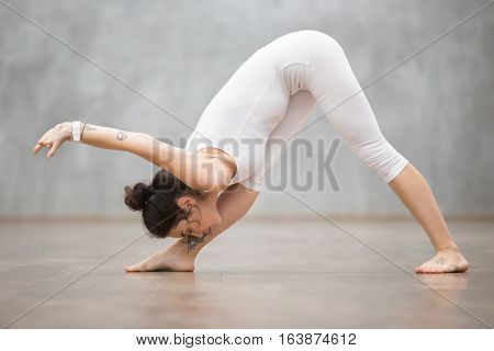 Portrait of beautiful young woman wearing white sportswear working out against grey wall, doing yoga or pilates exercise. Standing in Parsvottanasana, Pyramid, One Sided Fold pose. Full length