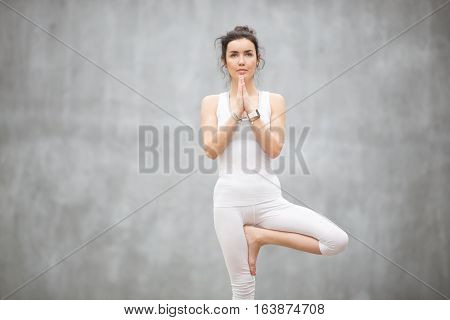 Portrait of beautiful young woman wearing white sportswear working out against grey wall, doing yoga or pilates exercise. Standing in Vrksasana, Tree pose