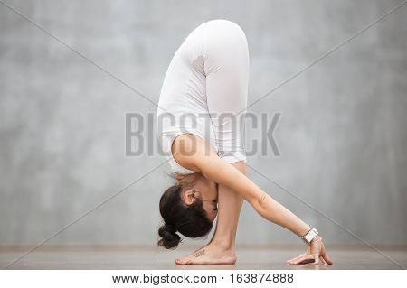 Portrait of beautiful young woman with tattoo on her foot meaning Wild kitty working out against grey wall, doing yoga or pilates exercise. Uttanasana, Standing forward bend. Full length photo