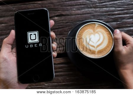 CHIANG MAITHAILAND - JUL 242016 : A MAN hand holding Uber app showing on iphone 6s with latte hot coffee cup on wood desk in coffee shop. Uber is smartphone app-based transportation network