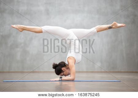 Portrait of beautiful young woman wearing white sportswear working out against grey wall, doing yoga or pilates exercise. Handstand with splits, variation of Pincha Mayurasana. Full length shot
