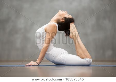 Side view portrait of beautiful young woman with tattoo on her foot meaning Wild kitty working out against grey wall, doing yoga or pilates exercise. King Cobra Pose, Raja bhudjangasana. Full length