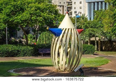 Holon Israel-July 21 2016: Bent painted metal art sculpture Clown by Yael Artsi is located at small city park in Neot Shoshanim district. Wide shot in bright sunny day on green trees and residential buildings facade background