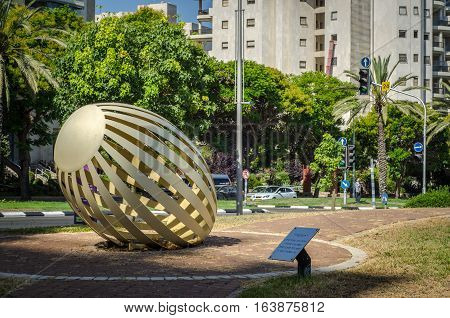 Holon, Israel-July 21, 2016:  Bent painted metal art sculpture Egg by Yael Artsi is located at small city park at Golda Meir Street. There are green trees, road, residential building facade and traffic light as background. Wide shot in bright sunny day