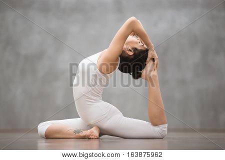 Side view portrait of beautiful young woman wearing white sportswear working out in fitness club or at home, doing yoga or pilates exercise. One Legged King Pigeon pose, Eka Pada Rajakapotasana