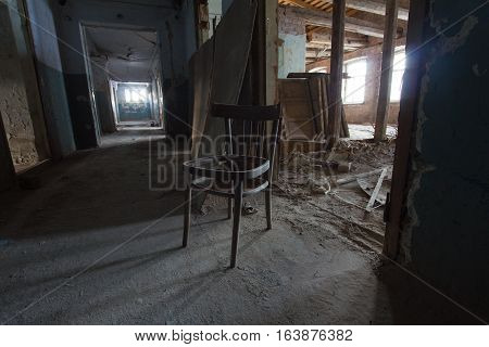 Abandoned old building - broken dusty chair in corridor, wide angle