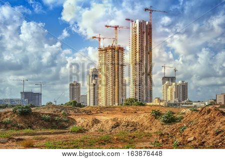 Bat Yam, Israel-May 27, 2016: View on part of the Sea Park huge real estate project. Some cranes work over new high-rise residential buildings on blue sky with perfect clouds background. Ground of construction site in front of it