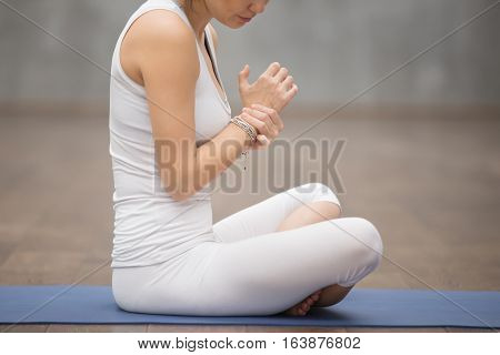 Young woman massaging her wrist while sitting on blue fitness mat, resting after working out or injured hand during careless sport practice, feeling pain and swelling in the joints. Close up