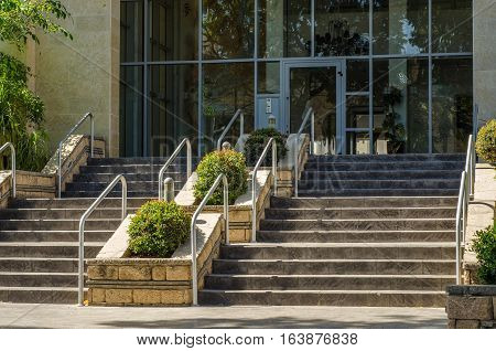 Wide stairway with metal hand railings and small shrubs growing in the flowerbed. It goes up to entrance of multi story residential building with large windows in lobby.