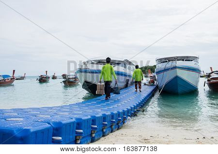 Closeup employees green shirt Unloading of speedboats.