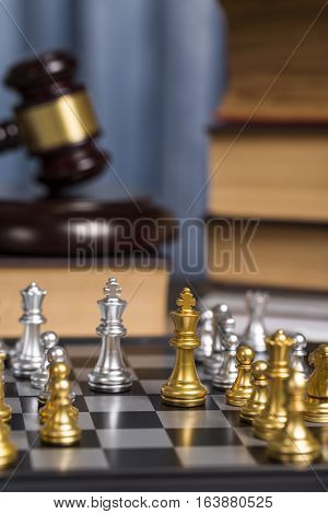 Close Up Golden Check On Lawyer Working Desk With Wooden Gavel And Law Book As Blurry Background.