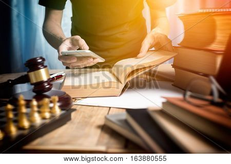 Young Man Lawyer Consulting With Teamwork By Video Conference On Mobile And Reading A Book Of Lawyer