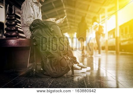 Young male asian traveler go to travel vacation by train the travel man with backpacking sitting at train station side view photography vintage style of image with sunlight effect.
