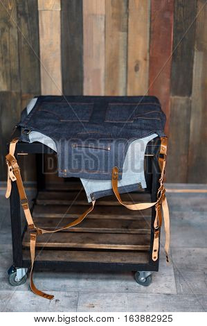 Denim bartender apron with leather straps on the table. Wooden background with free space