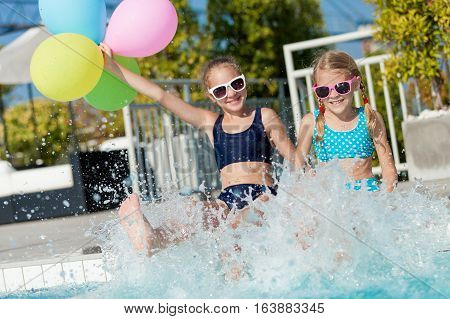 Two happy children with balloons playing on the swimming pool in aqua park at the day time. People having fun outdoors. Concept of friendly family and summer vacation.