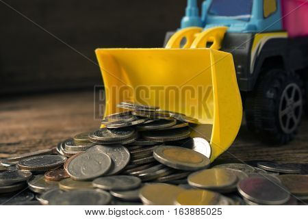 truck or bulldozer toy and coins concept idea for save money and business.