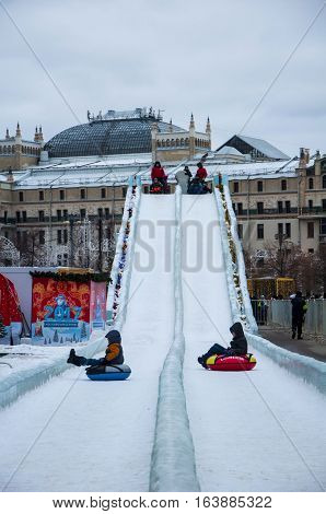Moscow, Russia - December 29, 2016: Children are rolling down by inner tubing from ice chute