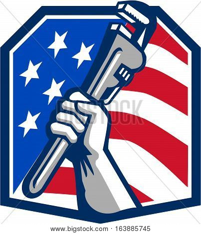 Illustration of a plumber hand clutching adjustable pipe wrench viewed from the side set inside heptagon shield crest shape with usa stars and stripes flag in the background done in retro style.
