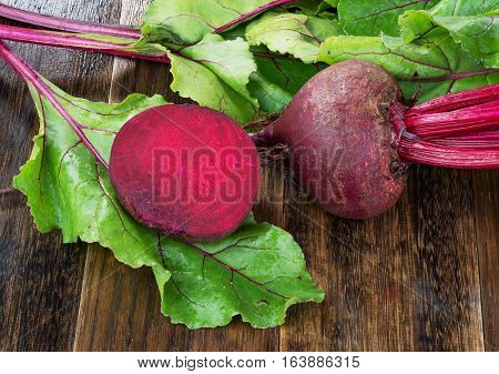 Fresh beetroots with leaves on wet wooden rustic table.Whole and cut beetroots