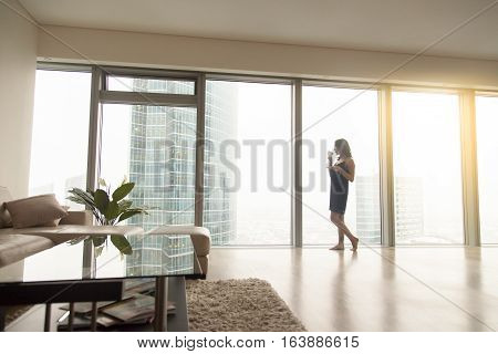 Full length view of happy young woman model standing near the window with a cup of coffee in luxury modern apartment, looking at cityscape after waking up in the morning, relaxing, dreaming