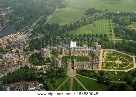 View from a plane of the historic Windsor Castle home of Queen Elizabeth II in Royal Berkshire. The River Thames passes to the left hand side and castle grounds stretch to the edge of the image. Cloudy Summer morning in June 2016.