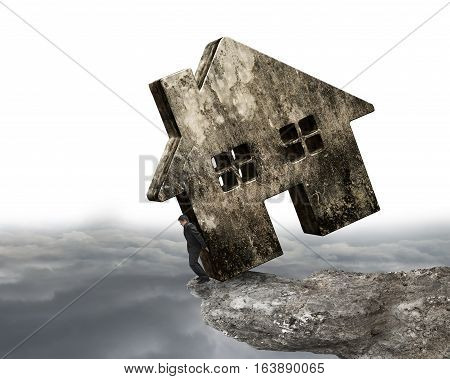 Man Holding Dirty Concrete House On Cliff Edge