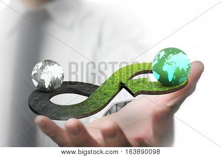 Green circular economy concept. Man's hand showing arrow infinity symbol with grass texture and two globes of different colors.