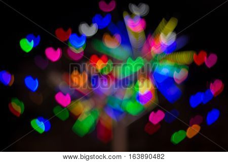 Defocused lights background. Heart bokeh  Bright colorful heart bokeh background. Multicolored blurry hearts on a black background.