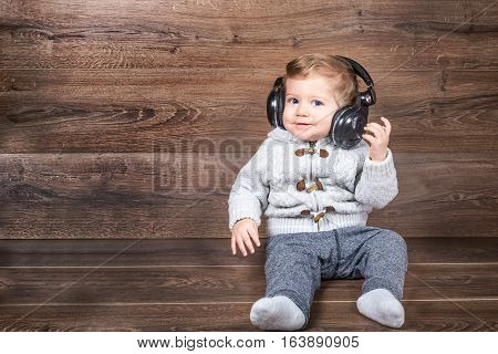 Baby boy smiling on wooden background with bluetooth/wireless headphones.