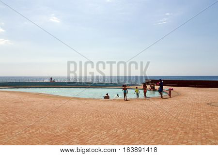 People Swimming In Seaside  Pool Against Ocean Skyline