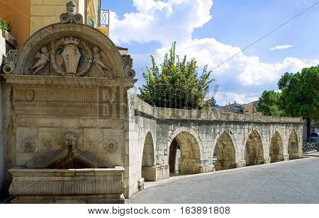 Italy Sulmona view of the Roman aqueduct with the Del Vecchio fountain in the foreground