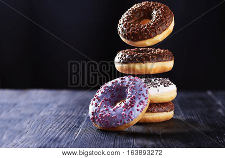 Donut with chocolate icing in motion falling on a tasty donuts with blue, chocolate and vanilla icing on a dark wooden background.