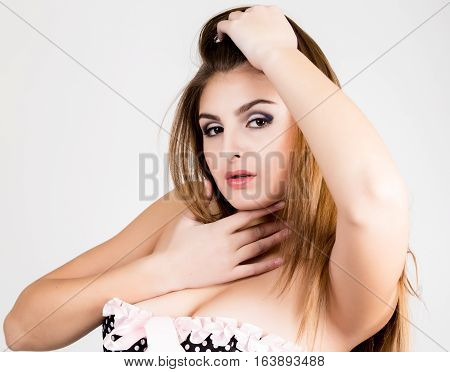 Portrait of a sensual young sexy woman wearing corset, touching her hair
