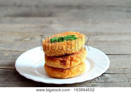 Fried vegetarian patties on a plate isolated on wooden background. Tasty patties made with boiled dried peas, eggs, flour and spices. Vegetarian food idea. Closeup