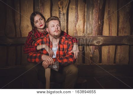 Style lumberjack. Woodcutter with a beard and mustache wearing a red shirt pants and suspenders and his girlfriend on a wooden background. Modern style.Loving couple of caucasian in style Lumberjack