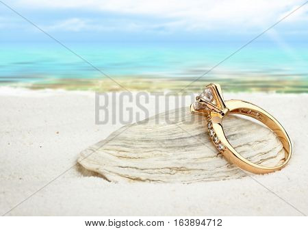 Jewellry ring with big diamond on sand beach soft focus