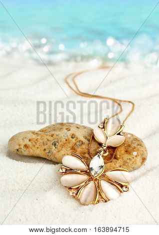 Golden jewellery pendant on sand beach soft focus