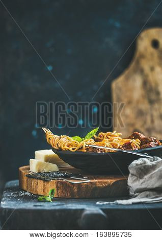 Italian pasta dinner. Spaghetti with meatballas, basil and parmesan cheese in black plate over rustic wooden board, dark blue plywood wall at background, selective focus, copy space. Slow food concept