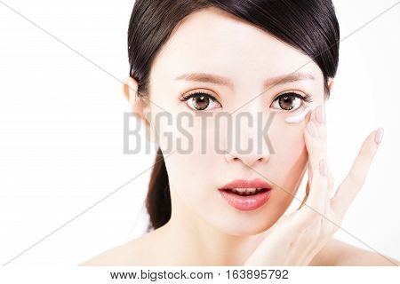young woman applying skin cream under eyes