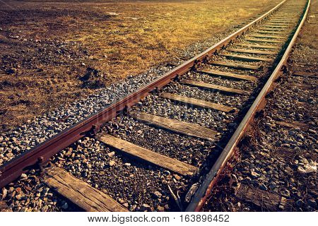 Old railroad track through grass field in sunset