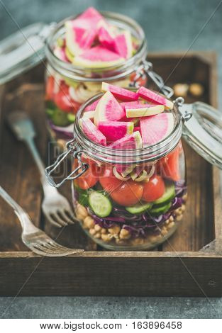 Healthy take-away lunch jars. Vegetable and chickpea sprout vegan salad in glass jars in wooden tray, grey concrete background, selective focus. Clean eating, vegetarian, raw food, dieting concept