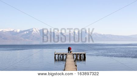 picture of an adult couple romance on a pier of lake prespa, macedonia
