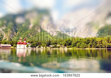 St. Bartholomew church in Konigssee National Park aroung Alps in summer Germany. Miniature tilt shift lens effect.