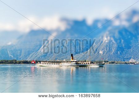 A boat floating in Geneva lake in Switzerland. Miniature tilt shift lens effect.