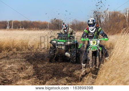 KHABAROVSK RUSSIA - OCTOBER 23 2016: Enduro bike rider and ATV in green colors on a field with dry grass in autumn.