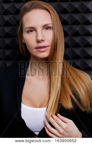 Brown-eyed woman in black jacket on black empty background