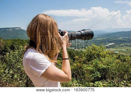 Cute young female wildlife photographer during safari making photos of deer